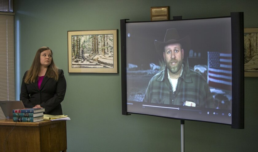 Attorney Lissa Casey, attorney for Ammon Bundy, listens to a recorded statement by Bundy as an image of him is shown on a screen, in Eugene, Ore., on Thursday, Feb. 4, 2016. The statement was recorded during a telephone conversation between Bundy and his attorneys, Casey and Mike Arnold, from the M
