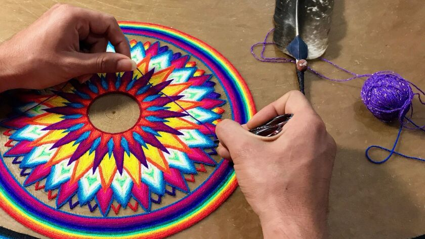 Huichol yarn painter Cilau Valadez works at the Galeria Tanana in Sayulita