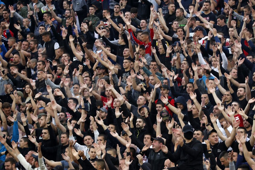 In this Wednesday, June 10, 2020. photo, Red Star fans support their team during a Serbian National Cup semi final soccer match between Partizan and Red Star in Belgrade, Serbia. Red Star Belgrade soccer club director Zvezdan Terzic says he has tested positive for the coronavirus, days after the Serbian champions played matches in front of thousands of fans despite the pandemic. (AP Photo/Darko Vojinovic)