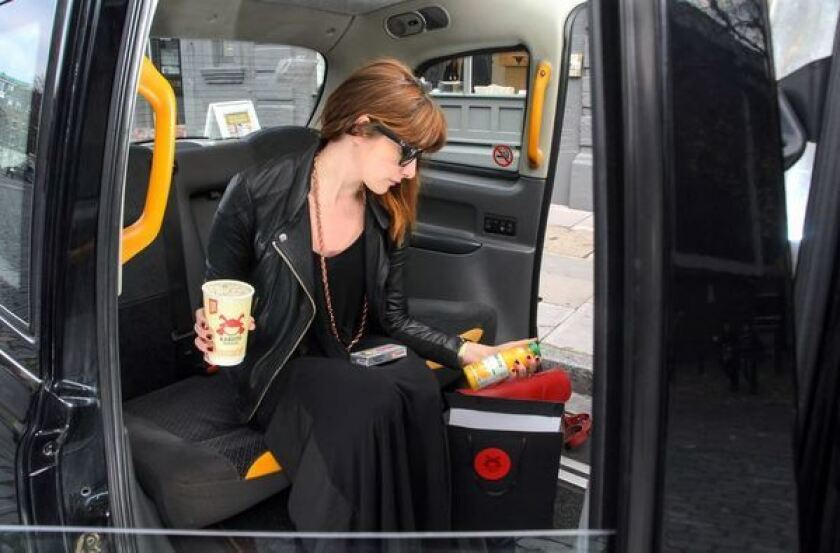 A woman sits in a Kab-u-to work hangover taxi and examines the contents of a hangover pack, including noodles orange juice, headache medicine, breath mints and sunglasses.