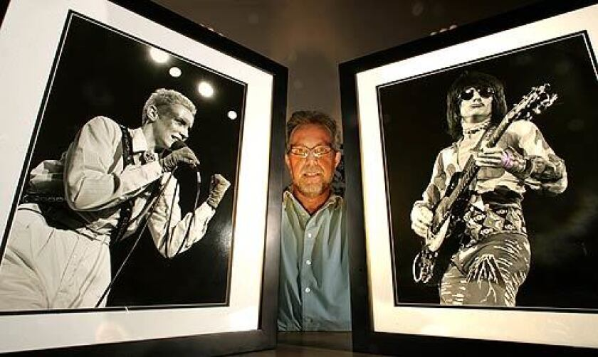Greg Papazian holds photographs he took of two of his favorite rock musicians: Annie Lennox, taken in 1983 at the Palace Theatre in Hollywood, and Ron Wood, taken at the Anaheim Convention Center in 1973.