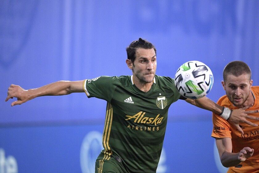 CORRECTS TO ADAM LUNDKVIST NOT ADAM LUNDKQVIST - Portland Timbers midfielder Diego Valeri, left, and Houston Dynamo defender Adam Lundkvist compete for a ball during the first half of an MLS soccer match Saturday, July 18, 2020, in Kissimmee, Fla. (AP Photo/Phelan M. Ebenhack)
