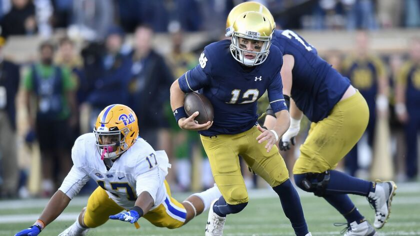 Notre Dame quarterback Ian Book scrambles to avoid the tackle from Rashad Weaver #17 of the Pittsburgh Panthers in the second half at Notre Dame Stadium on October 13, 2018.
