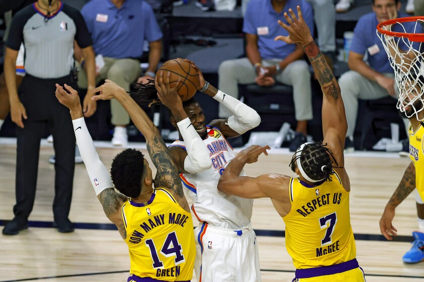 Oklahoma City Thunder's Nerlens Noel is defended by Lakers' Danny Green and JaVale McGee during the second quarter.