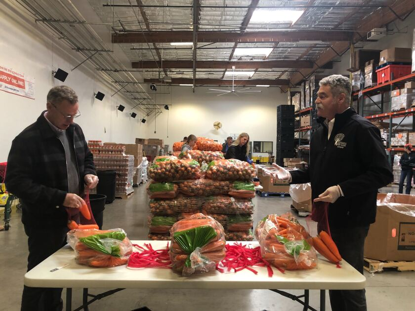 Rep. Scott Peters prepares food to be given to those in need with San Diego Food Bank President & CEO James Floros.