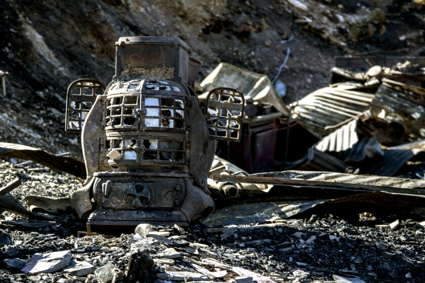 A fire-blackened old stove with broken glass panes and two small doors ajar sits among other charred debris