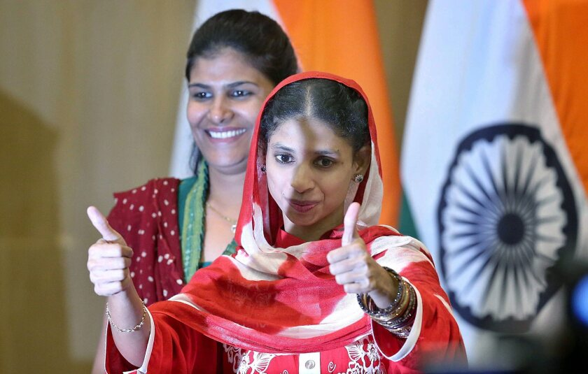 An Indian woman named Geeta (with thumbs up), who is deaf and mute, gestures during a news conference in New Delhi, India, on Monday.