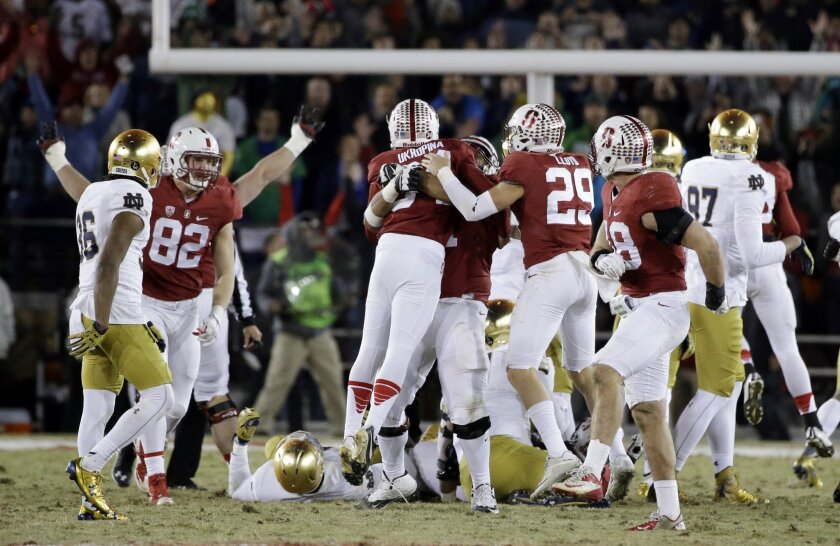 Stanford's Conrad Ukropina (34) is hugged by teammates after hitting a 45-yard field goal as time expired to give Stanford a 38-36 win over Notre Dame in an NCAA college football game Saturday, Nov. 28, 2015, in Stanford, Calif. (AP Photo/Marcio Jose Sanchez)