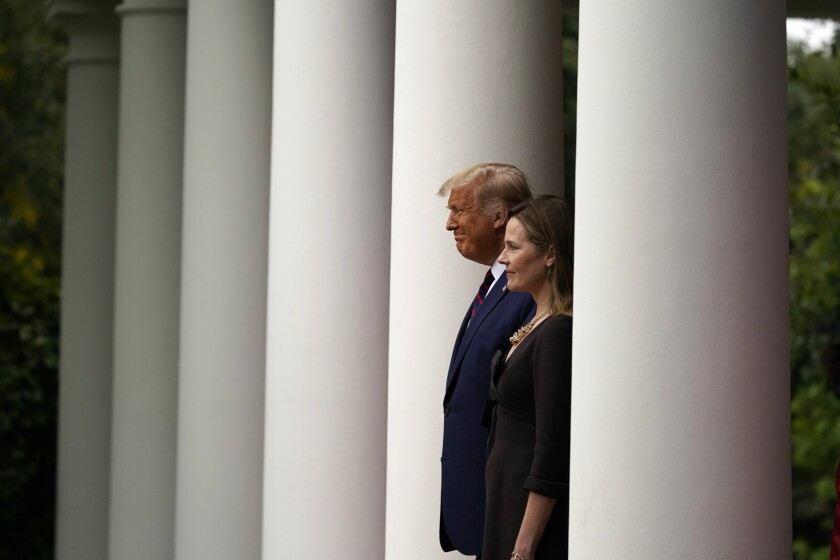 President Donald Trump walks with Judge Amy Coney Barrett to a news conference.
