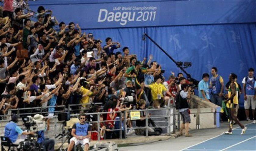 Spectators take photos of Jamaica's Usain Bolt, right bottom, during a victory lap after winning the gold in the Men's 200m final at the World Athletics Championships in Daegu, South Korea, Saturday, Sept. 3, 2011. (AP Photo/Shuji Kajiyama)