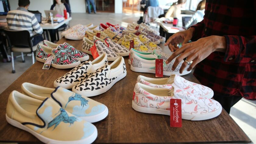 An array of creative colorful Bucketfeet shoes are displayed Feb. 3, 2015, at the company's headquarters in Chicago. E-commerce retailer Threadless has acquired Bucketfeet and will produce its on-demand shoes.