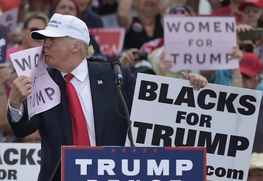 """Donald Trump kisses a """"Women for Trump"""" sign during a rally in Lakeland, Fla., in October."""