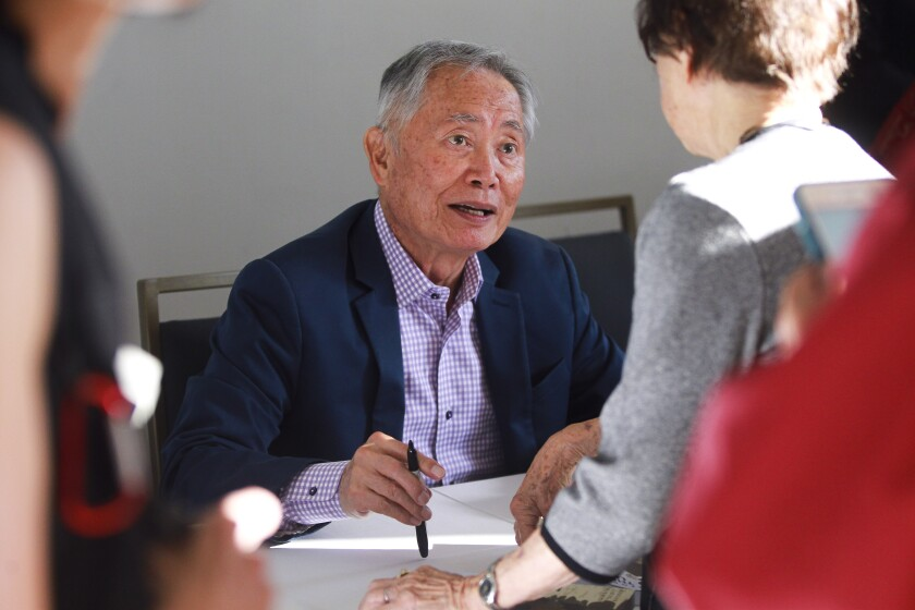 """George Takei, who played Sulu in Star Trek, autographs his book """"They Called US Enemy"""", a book about he and his family being placed in Japanese internment camps after the Japanese bombed Pearl Harbor, for people during the Never Forget, Our 90th Anniversary Gala, put on by the San Diego Japanese American Citizens League, at the Town & Country Hotel and Convention Center on Saturday, September 14, 2019 in San Diego, California."""