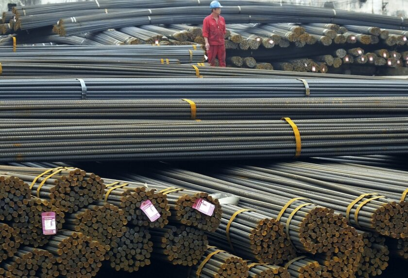 In this April 25, 2016 photo, a man works in a steel market in Yichang in central China's Hubei province. China accused the United States on Thursday, May 26, 2016 of hampering trade after Washington imposed duties of up to 450 percent on Chinese steel in its latest response to a flood of low-price