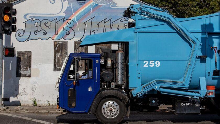 A trash truck from Rainbow Environmental Services on Nichols Lane in Huntington Beach passes the 1934 Japanese Presbyterian Church.
