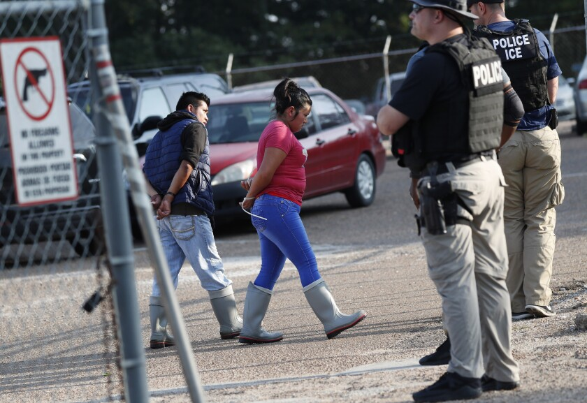 Two people are taken into custody at a Koch Foods Inc. plant in Morton, Miss., on Wednesday.