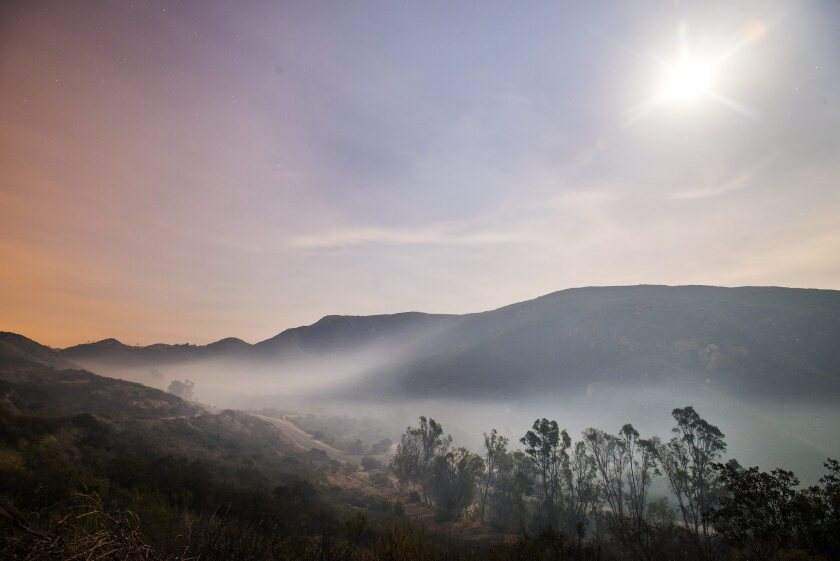 Smoke from the fires in San Marcos and Escondido lays down at dawn due to subsiding winds near Elfin Forest Road in San Diego County.