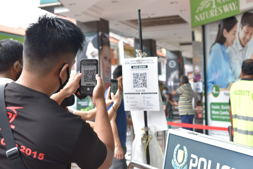 A man scans a QR code to record his entry at a shopping center in Singapore.
