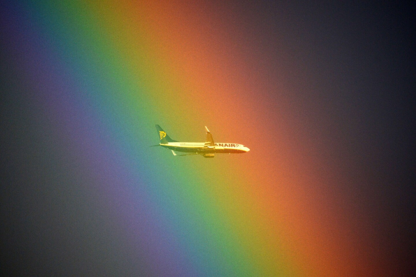 A Ryanair plane flies in front of a rainbow over Rome.