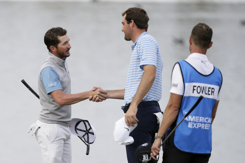 Andrew Landry shakes hands with Scott Scheffler, right, after winning The American Express golf tournament on the Stadium Course at PGA West.