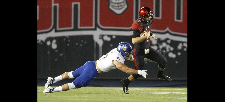 The Aztecs quarterback Ryan Agnew runs as San Jose State's Jesse Osuna tackles during the first quarter.