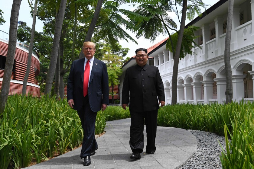 President Trump walks with North Korean leader Kim Jong Un during a break in talks at their historic summit in Singapore on June 12, 2018.