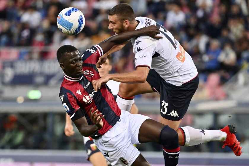 Bologna's Musa Barrow, left, competes for the ball with Genoa's Mattia Bani during the Serie A soccer match between Bologna and Genoa, at the Renato Dall'Ara stadium in Bologna, Italy, Tuesday, Sept. 21, 2021. (Massimo Paolone/LaPresse via AP)