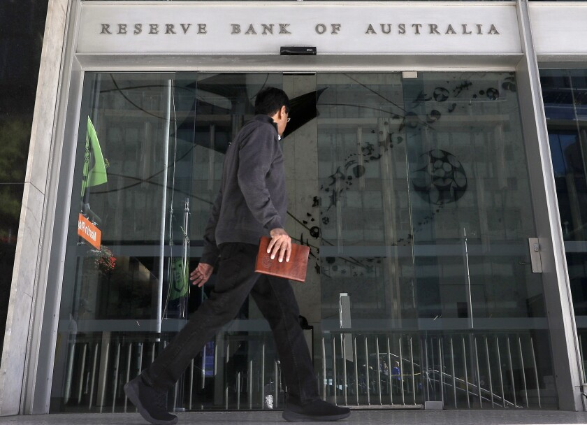 A man walks past the Reserve Bank of Australia in Sydney, Tuesday, Oct. 1, 2019. Australia's central bank cut its benchmark interest rate by a quarter of a percentage point for the third time since June to a new record low of 0.75%, seeking to boost a flagging economy. (AP Photo/Rick Rycroft)