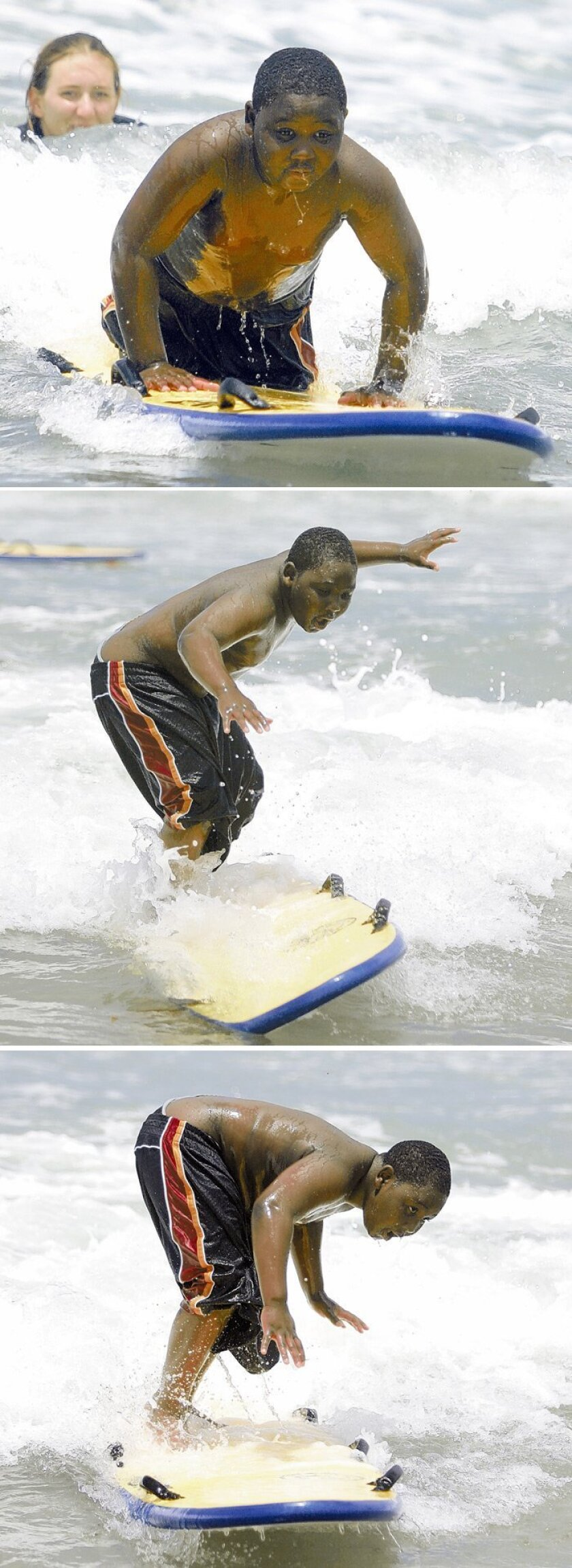 "With some help from San Diego lifeguard Emily Nanninga, Tashawn Lucas, 9, was able to stand up on a surfboard Friday at South Mission Beach. More than 300 children from King-Chavez school participated in the ""Bridge to the Beach"" program sponsored by the San Diego Junior Lifeguard Foundation."