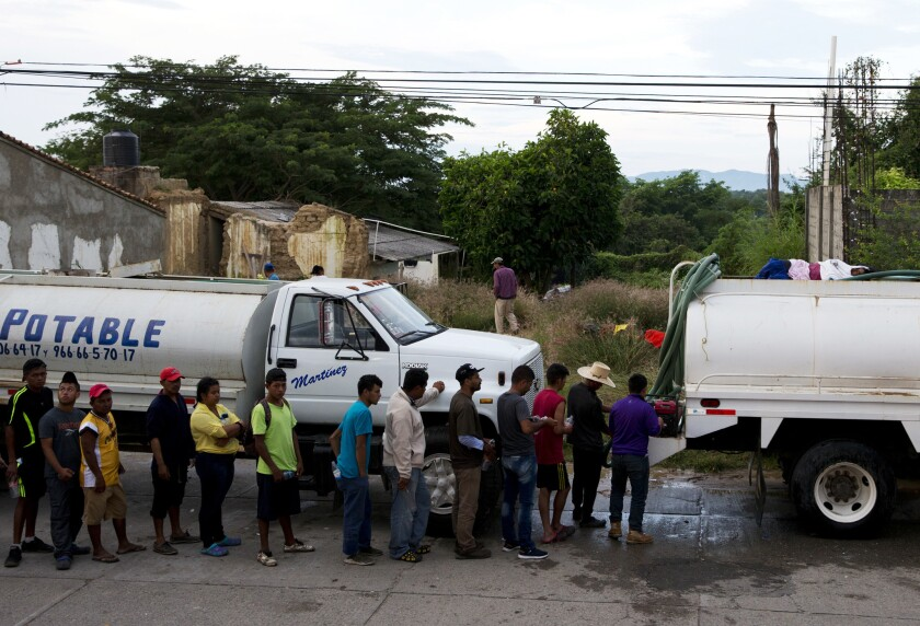 Migrants wait in line beside a water truck to brush their teeth and fill water bottles, as a caravan of Central Americans trying to reach the U.S. border halts for a rest day in San Pedro Tapanatepec, Oaxaca state, Mexico,