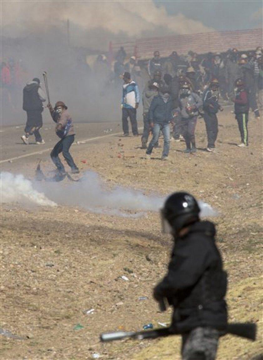 Mineros independientes chocan con la policía y huyen de gases lacrimógenos durante protestas en Panduro, Bolivia.
