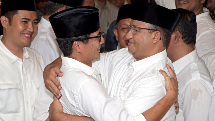 Jakarta governor candidate Anies Baswedan, right, hugs his running mate, Sandiaga Uno, after exit polls showed him winning a runoff election to lead Indonesia's capital.