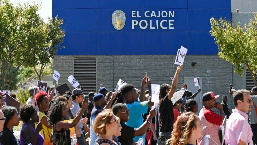 Protesters march past the headquarters of the El Cajon Police Department in downtown El Cajon, Calif., Saturday Oct. 1, 2016, in reaction to the fatal police shooting of Alfred Olango, an unarmed black man.