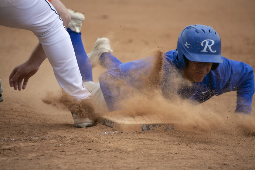 Ramona's E.J. Edelman dives safely back to first base during the Bulldogs' Lions Tournament win over Valhalla on Tuesday.