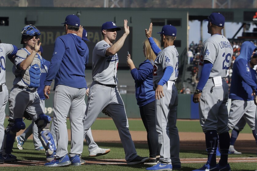 Dodgers players celebrate after defeating the San Francisco Giants on Sunday in San Francisco.