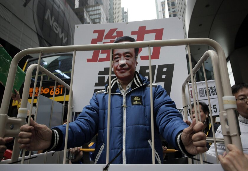 FILE - In this Jan. 10, 2016 file photo, a protester wearing a mask of missing bookseller Lee Bo sits in a cage during a protest against the disappearances of booksellers in Hong Kong. Hong Kong police said late Monday, Jan. 18, 2016 that they received notice from Guangdong province's public securi