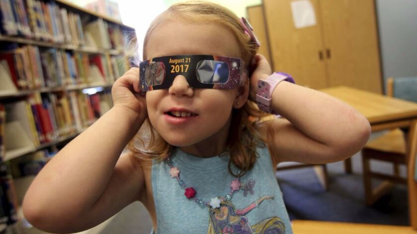 Emmalyn Johnson, 3, tries on a pair of eclipse glasses at Mauney Memorial Library in Kings Mountain,