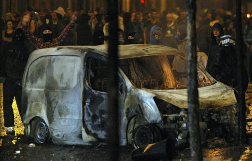 """Rioters attack police lines from behind a burnt out car as a large crowd of Nationalists gather on the Broadway in west Belfast, Northern Ireland Monday, July 11, 2011. Northern Ireland's divisive annual holiday called """"The Twelfth,"""" when tens of thousands of Protestants parade across the British territory, got off to a violent start Tuesday with riots in several parts of Belfast. (AP Photo/Colm O'Reilly)"""
