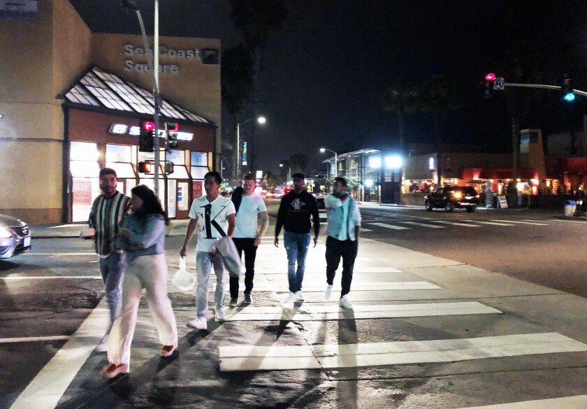 File photo: People walk in Pacific Beach without masks in June 2020.