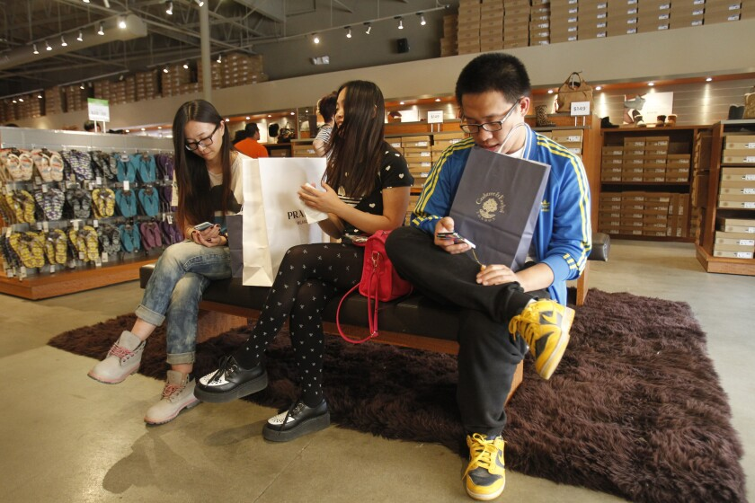 Bam Wang, left, Zhe Chen and Shuai Wu wait for a friend shopping at the UGG store at the Desert Hills Premium Outlets in Cabazon, Calif. Spending by foreign visitors increased by 5% in the first eight months of 2014.
