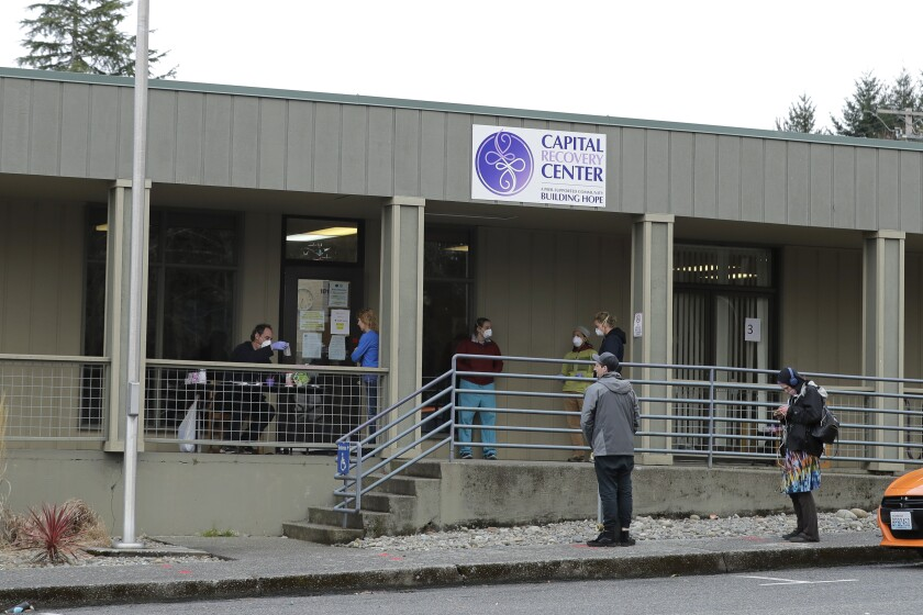 Patients line up to pick up medication at a clinic in Olympia, Wash.