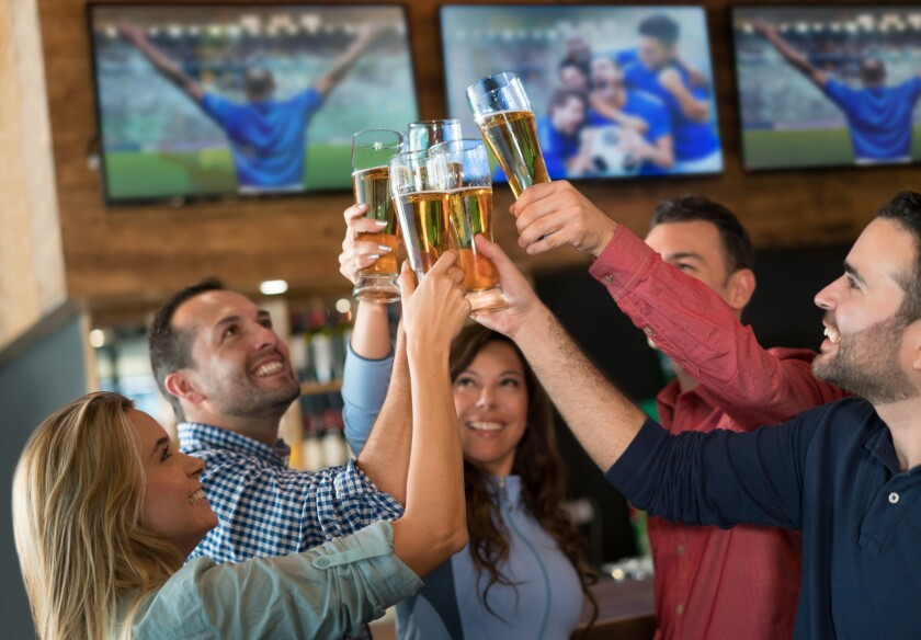 Happy group of Latin American friends watching a football game and making a toast at a sports bar