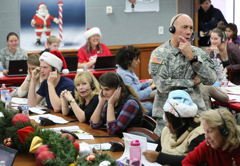 U.S. Northern Command Chief of Staff Maj. Gen. Charles D. Luckey and volunteers take phone calls from children around the world. A misprint in a newspaper advertisement kicked off NORAD's Santa-tracking activities 60 years ago.