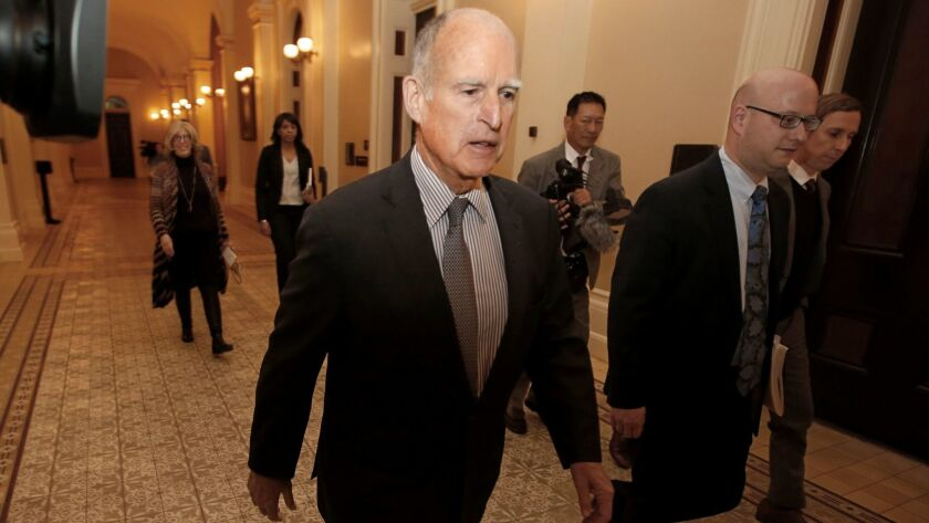 California Gov. Jerry Brown returns to his office after meeting with the Senate Democratic Caucus to