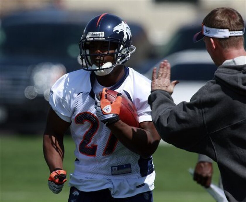 Denver Broncos first-round draft pick Knowshon Moreno, left, runs past coaches while taking part in a drill during the team's football minicamp at the Broncos' headquarters in the southeast Denver suburb of Englewood, Colo., on Sunday, May 3, 2009. (AP Photo/David Zalubowski)
