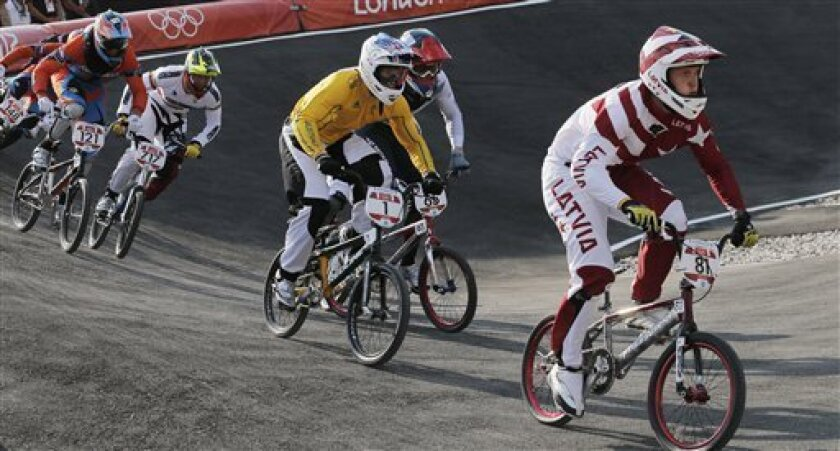 Latvia's Maris Strombergs leads other cyclists while competing in the BMX cycling men's final run during the 2012 Summer Olympics in London, Friday, Aug. 10, 2012. Strombergs won his second straight Olympic gold medal in BMX on Friday, taking the lead out of the starting gate and never relinquishing it. (AP Photo/Christophe Ena)