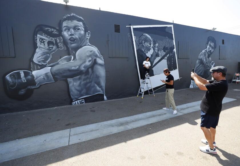 El muralista Paul Jiménez toma una fotografía de su compañera Signe Ditona y Carlos Barragan Jr.
