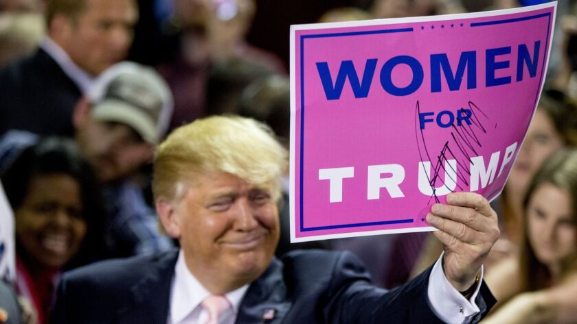 """Then presidential candidate Donald Trump holds a campaign sign that reads """"Women for Trump"""" after speaking at a rally in Valdosta, Ga. on Feb. 29, 2016."""
