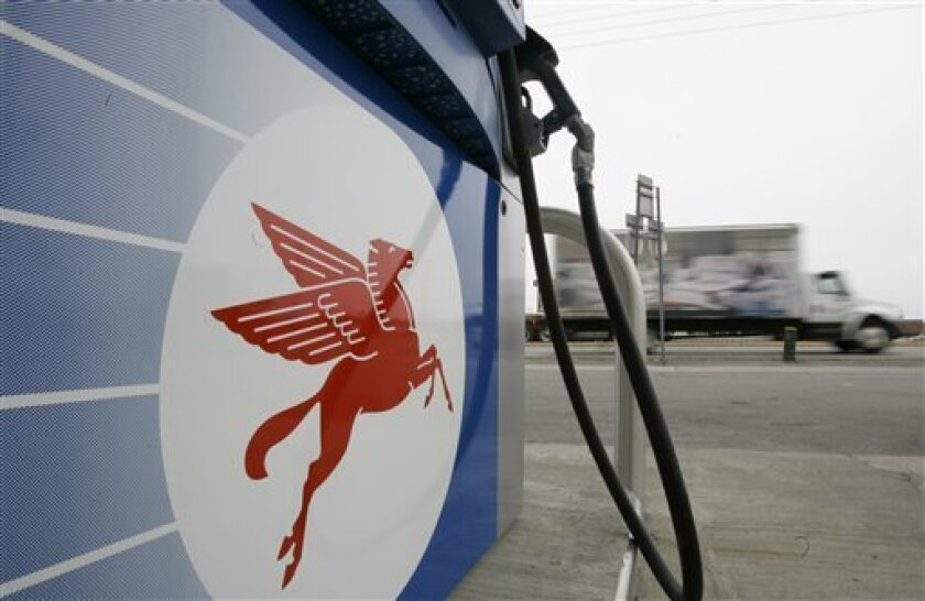 In this May 1, 2008 file photo, a truck passes a pump at an ExxonMobil station in Williamsville, N.Y.  