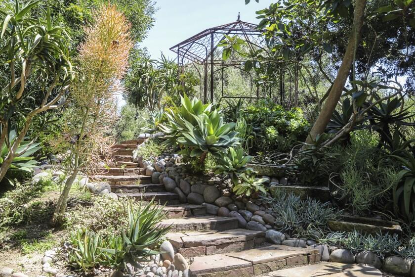 A metal gazebo sits atop a mound in the Ryans' garden.